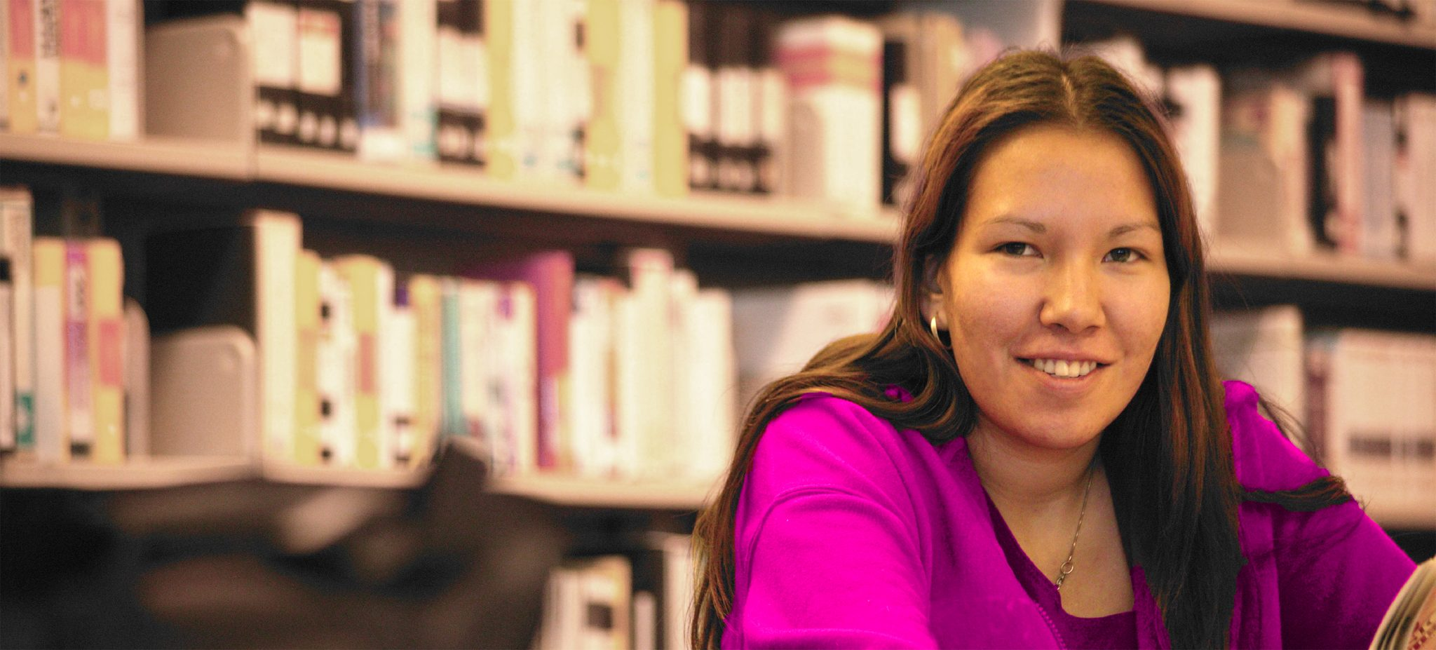 A young indigenous woman in a library.