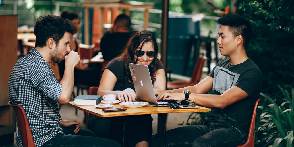 Two young men and a young woman sit outside of a cafe working on laptops.