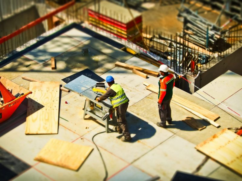 A birds eye image of two construction workers working on site.