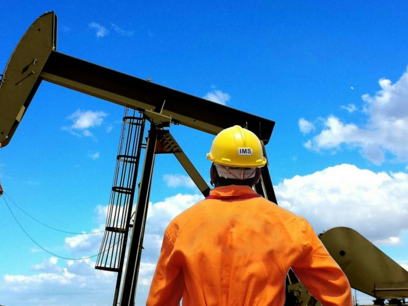A worker looking up at an oil rig.