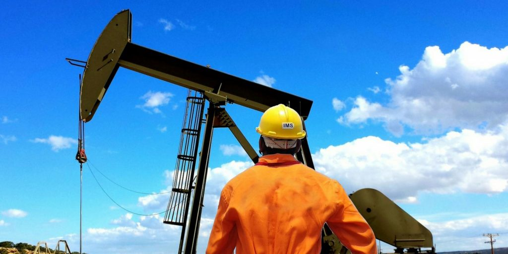 Photo of an individual looking at an oil rig.