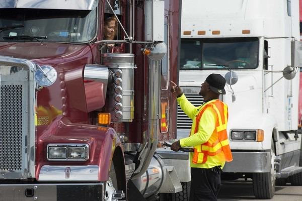 A man speaking with a truck driver.