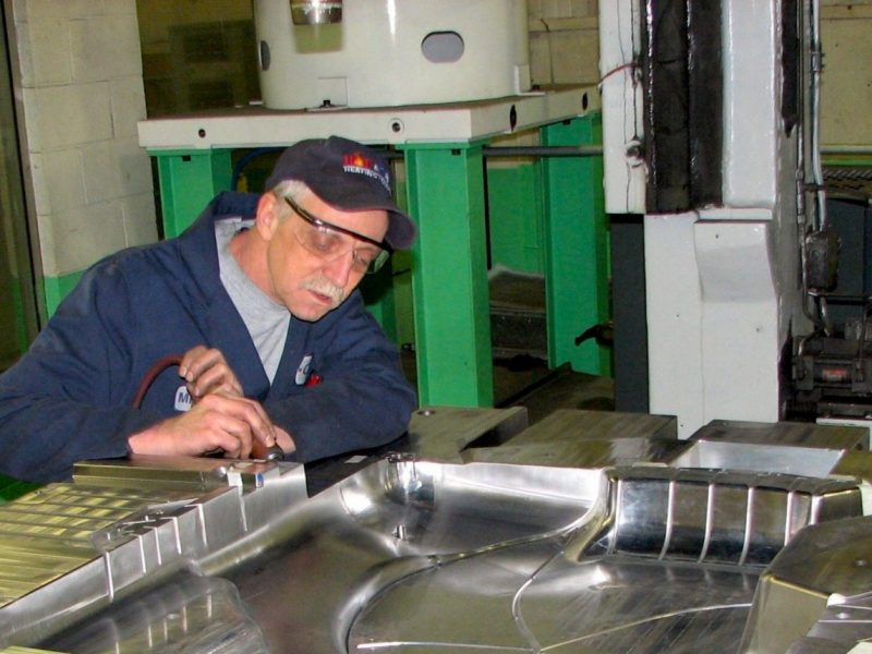 A technician working on an injection mold