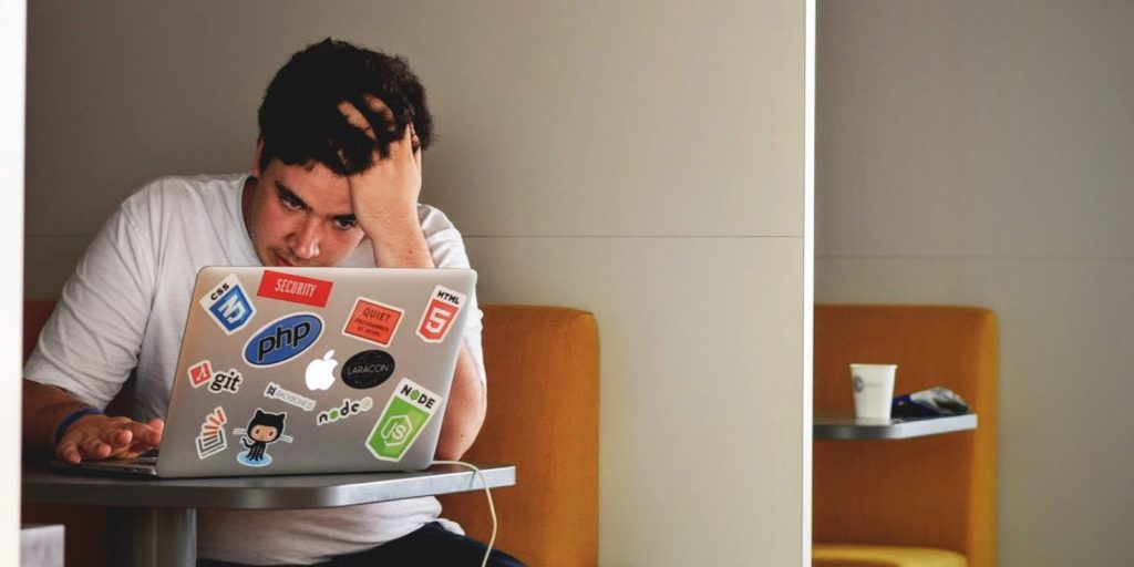 An individual stressfully holding their head up as they look at their laptop.