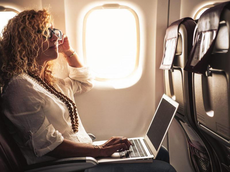 Photo of an Individual using a laptop on an airplane