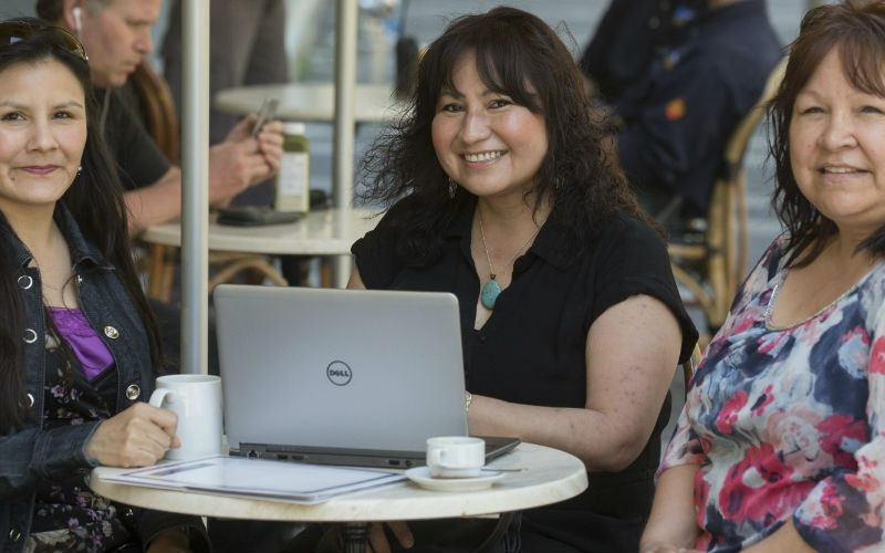 Three indigenious women smiling and sitting in front of a laptop in a cafe setting.