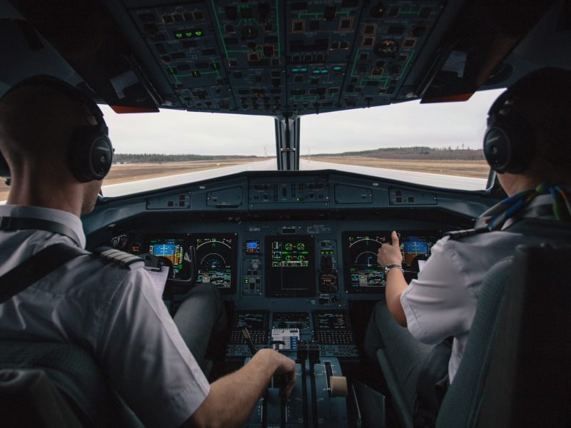 Two pilots sit in a cockpit on the runway preparing for flight.
