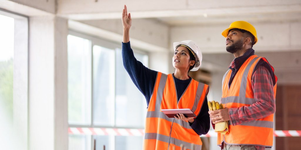Photo of a woman of Indian ethnicity holding a digital tablet and talking to a young construction worker while pointing at something at the construction site.
