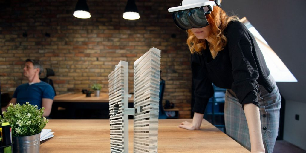 An individual wearing an augmented reality headset to visualize two office towers