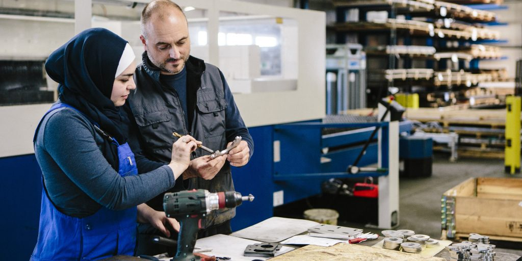 teamwork: technician explains a work tool to a young woman in a workshop