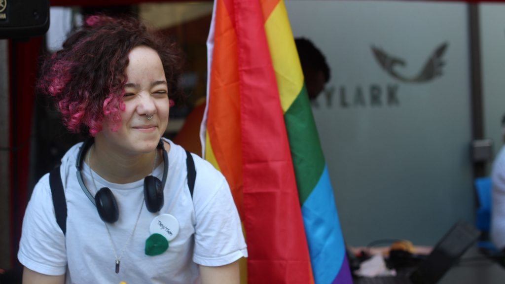 Young person in front of Pride flag