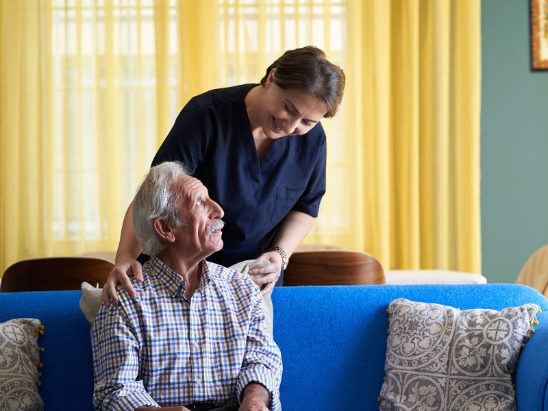 Standing care worker leaning in to smile at senior seated on a couch