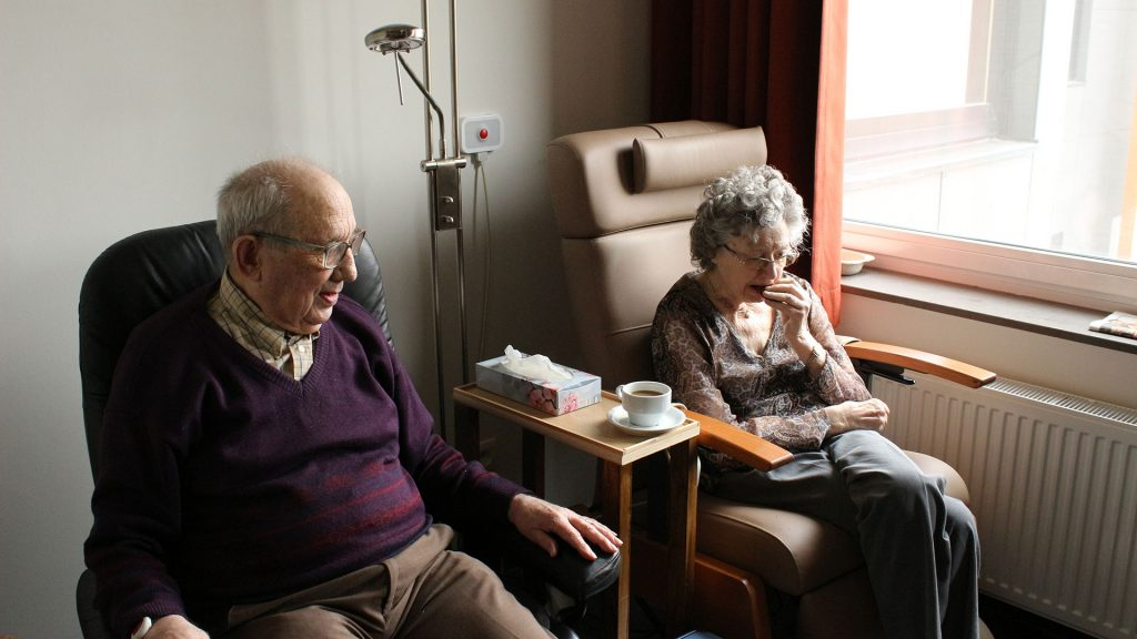 Two seniors sitting in armchairs in a hospital setting