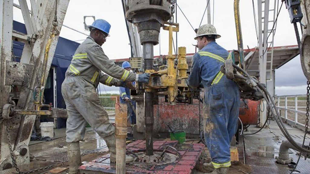 Two energy workers handling large machinery