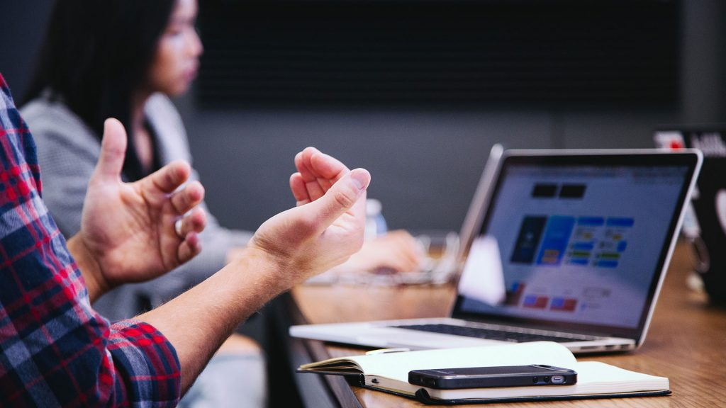 Hands gesticulating in front of open laptop; person on laptop in background