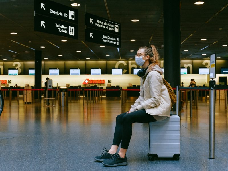 woman sitting on luggage at the Swiss airport