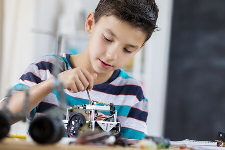 Young boy working on robot project