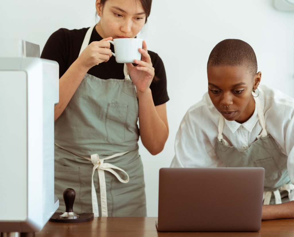 Two woman, one sipping coffee, both are looking at a laptop screen