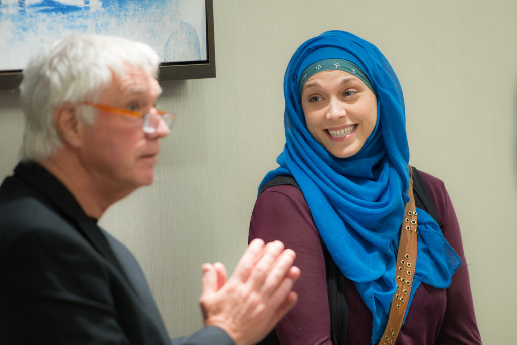Man speaking to a group while woman listens smiling.