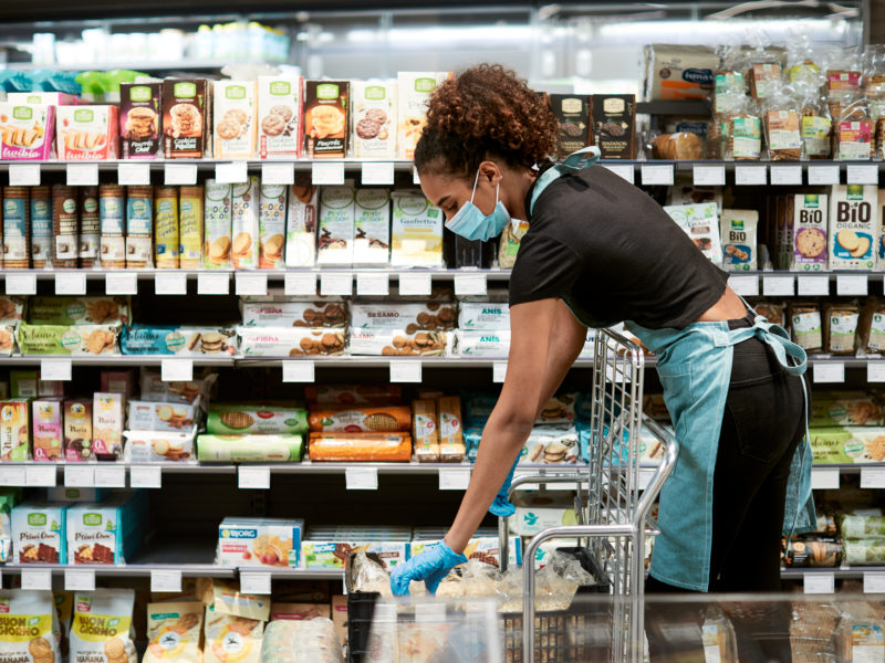 Young woman stocking inventory in grocery store with clinical mask on.