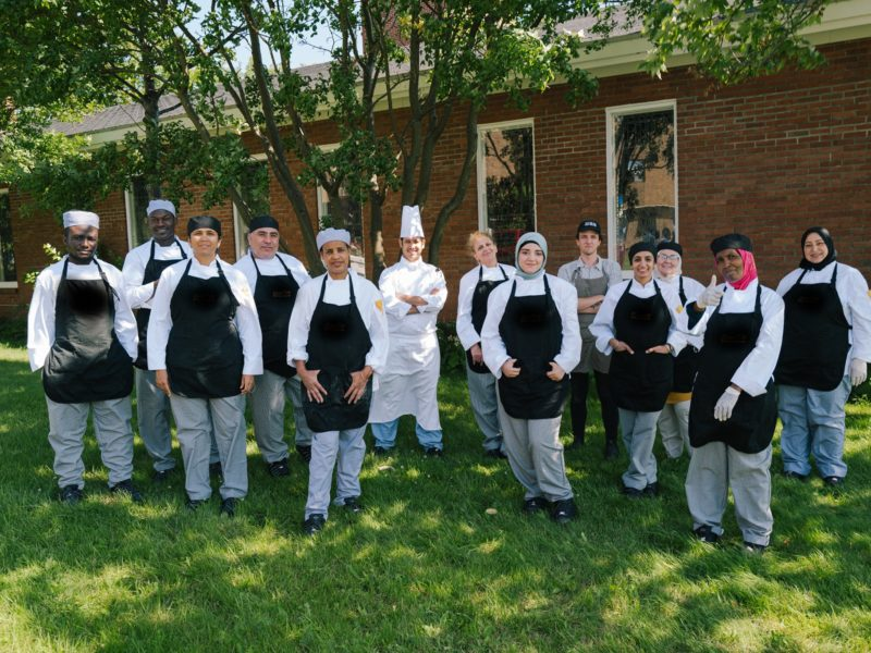 Group of diverse individuals wearing chef clothing in a class photo.