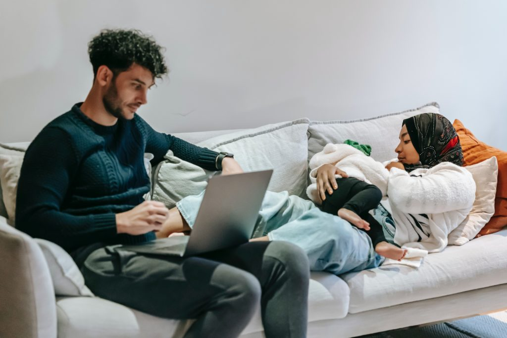 Father working on laptop near mother laying down with daughter.