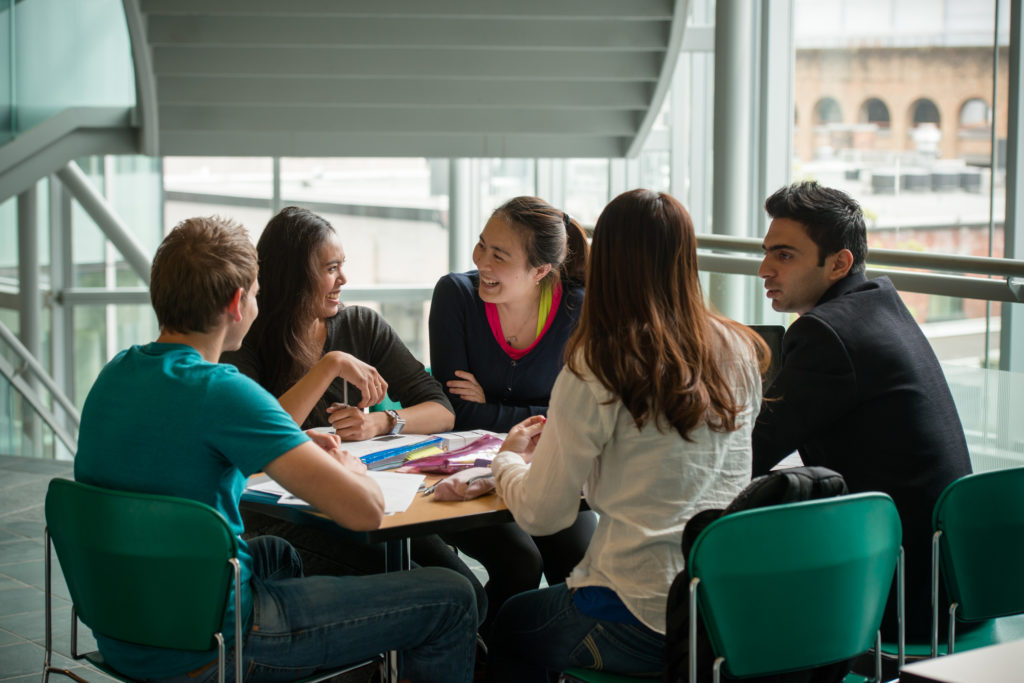 Group of students around a table smiling.