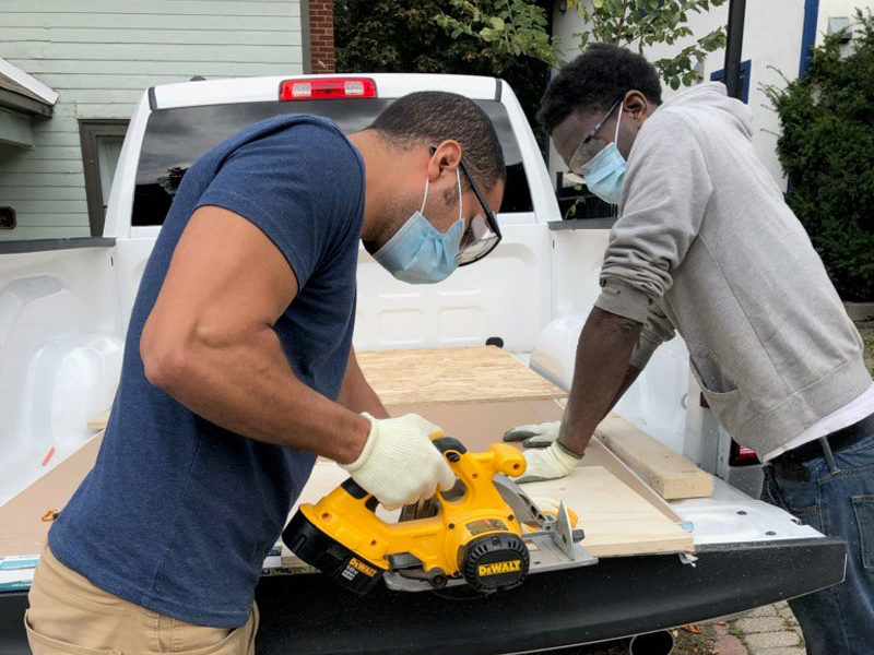 Two gentlemen sawing a piece of wood together.