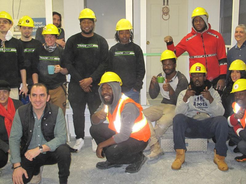Group photo of construction graduates wearing hard hats.