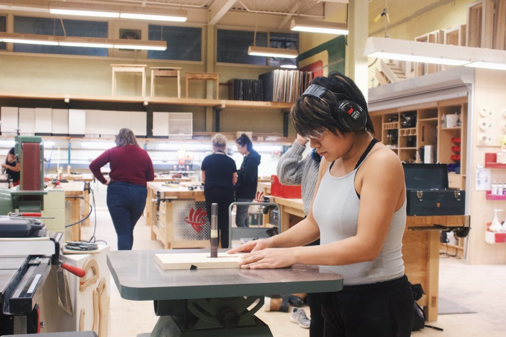 Young girl with headphones using a bandsaw in woodworking class.