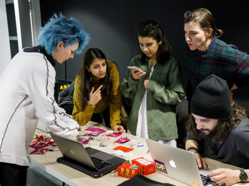 Group of textile students looking over samples of fabric.
