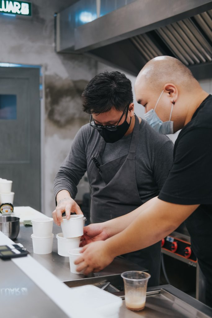 Two men packaging containers in a restaurant kitchen.