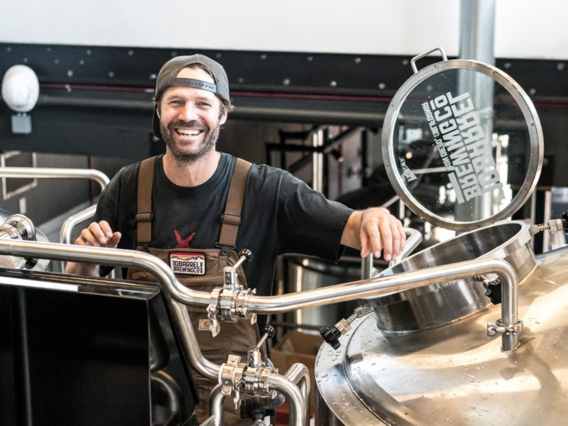 Man smiling while working in a beer brewing factory.