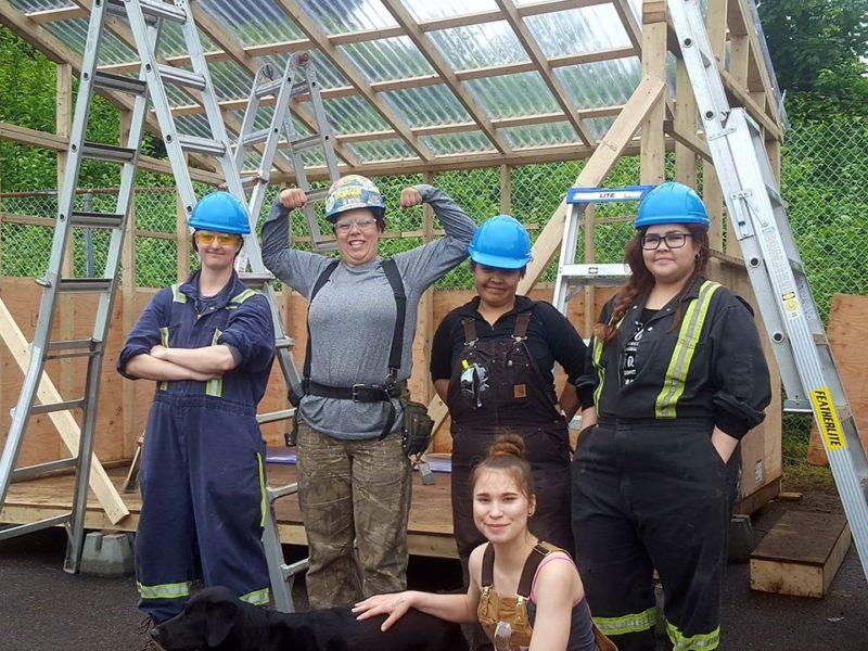 Women in construction gear standing infront of a building frame.