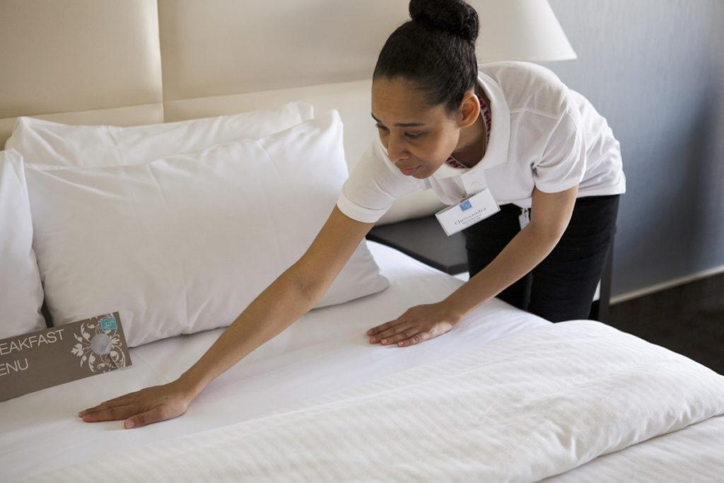 Hotel staff folding sheets.