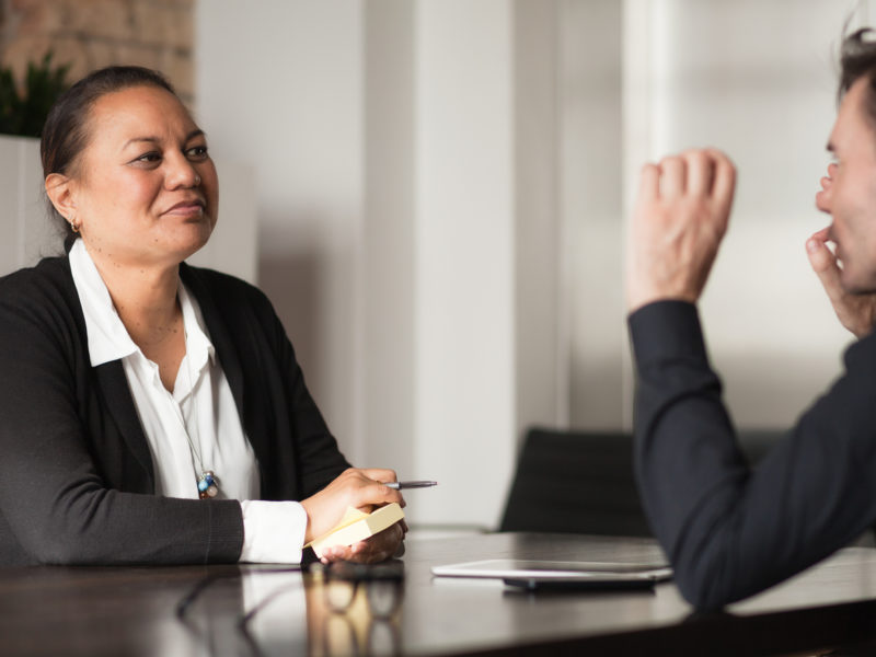 Two individuals in a meeting room having a discussion.