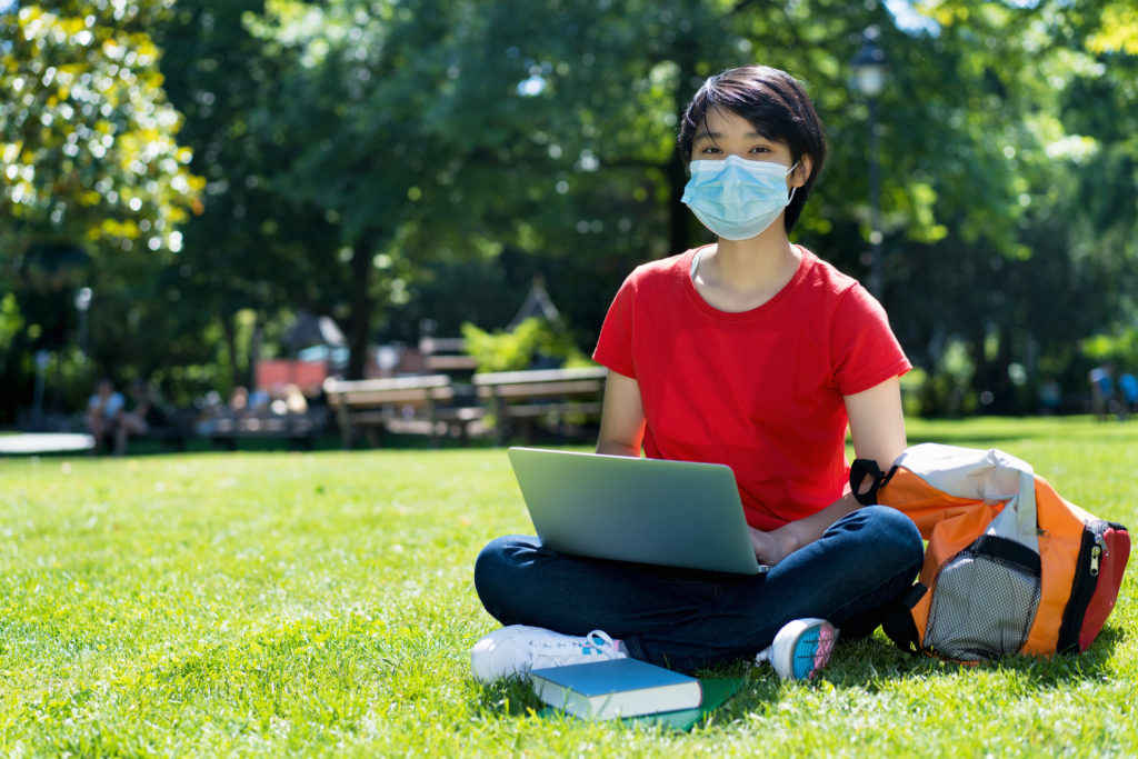 Student sitting outside of university campus with a clinical mask on.