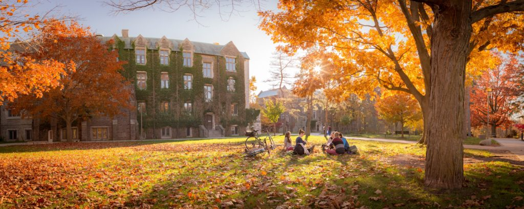 A group of students sitting outside on university campus.