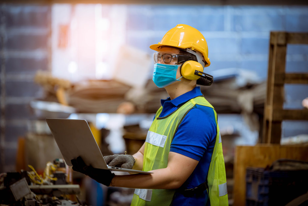 Construction worker holding laptop and wearing a clinical mask.