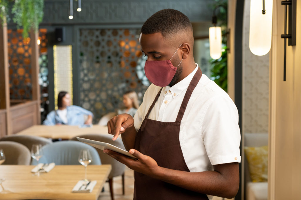 A server taking an order in a restaurant with a face mask on.