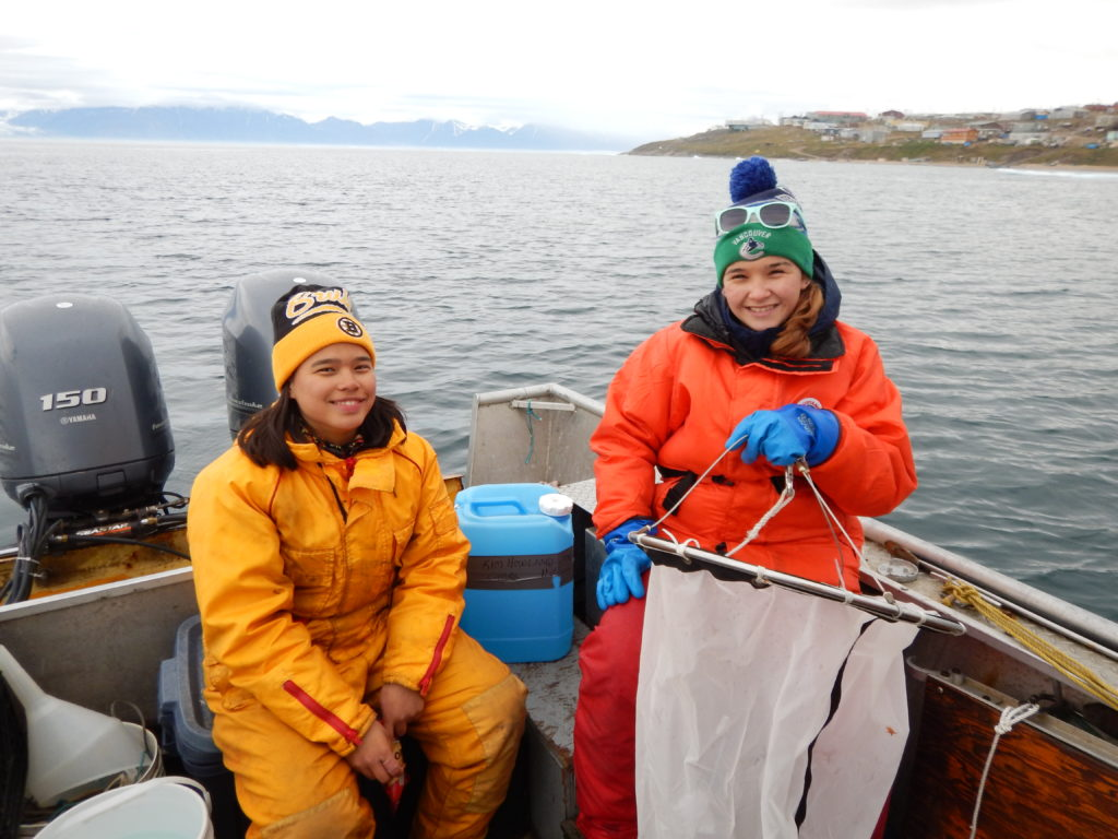 Two young individuals in a boat holding up a plankton net.