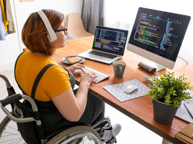 Woman in wheelchair working from home looking at dual computer screens.