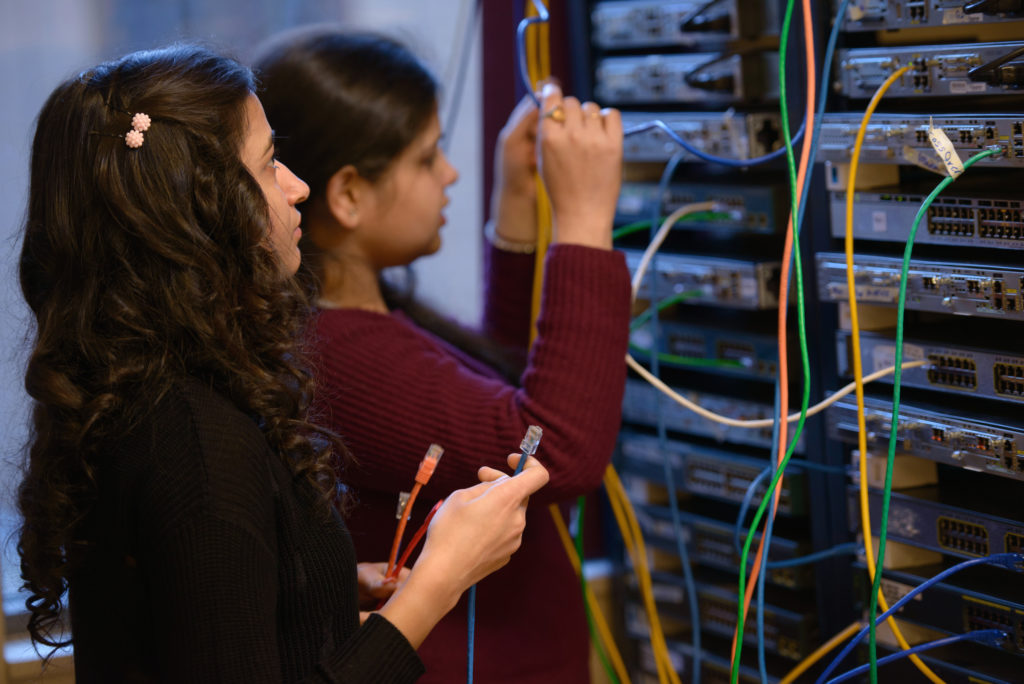 Two young women working on connecting the servers with wires.