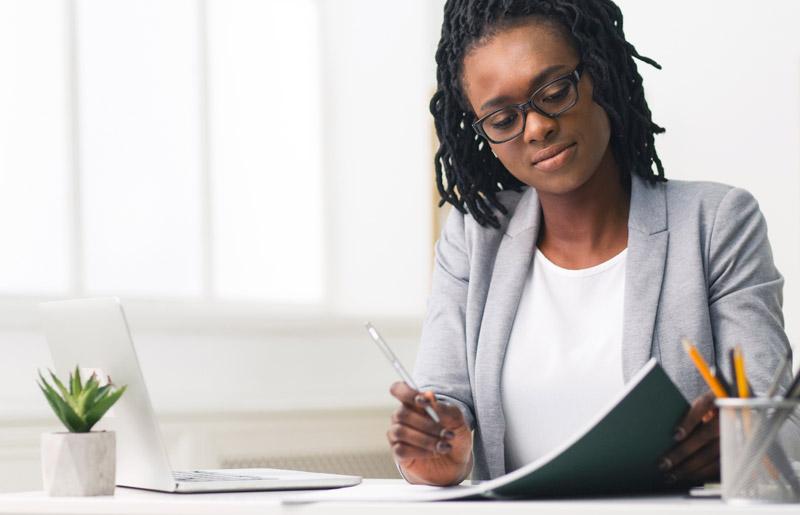 Woman in blazer writing in notebook.