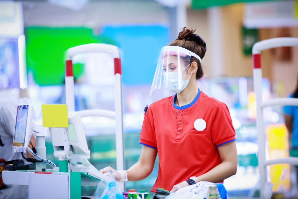 Grocery store cashier wearing a medical mask and face shield.