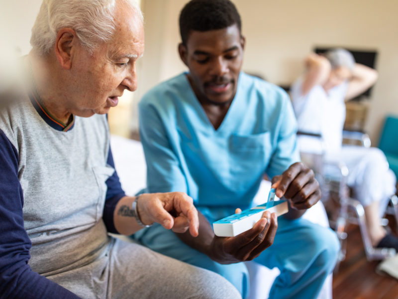 A personal support worker handing medication to an elderly man.