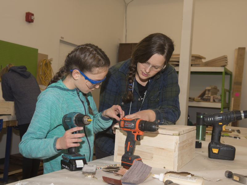A woman teaching a younger girl how to drill and build a wooden box.
