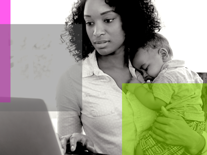 Mother holding child close to her chest while scrolling through a laptop