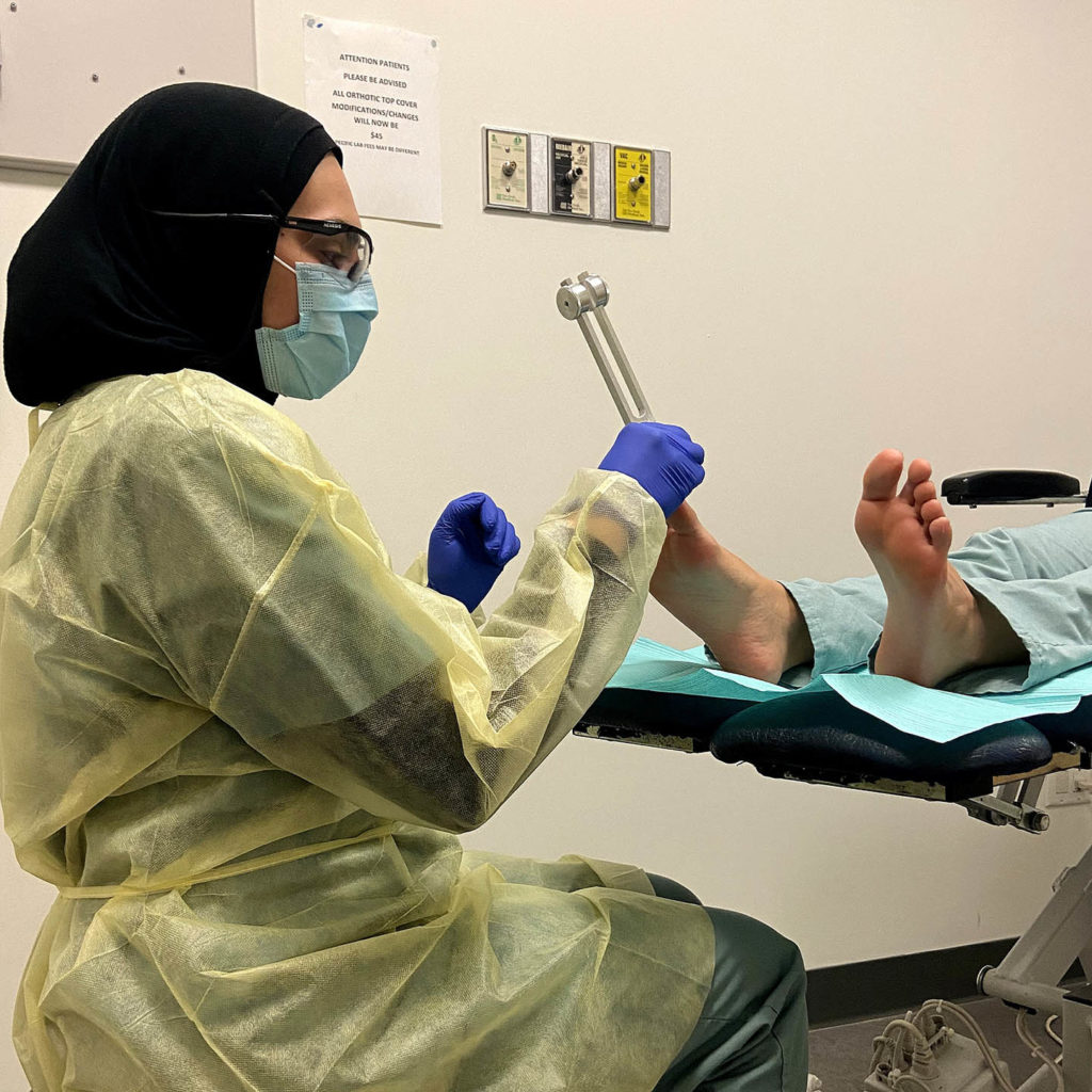 Health care professional providing care to a person's foot.