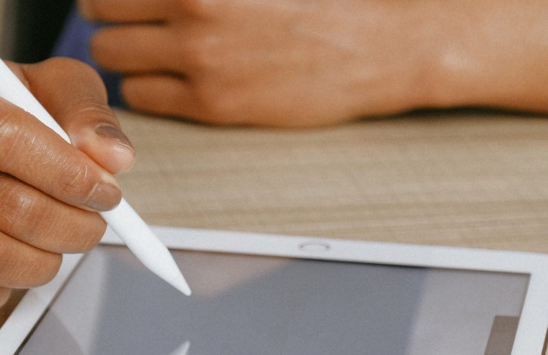 hand holding a stylus and writing on a tablet